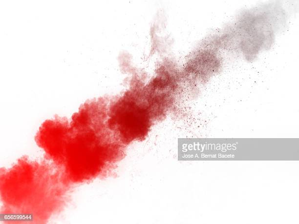 Explosion of a cloud of powder of particles of  red and orange color on a white background