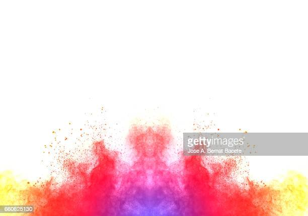 Explosion of a cloud of powder of particles of  red and pink color on a white background