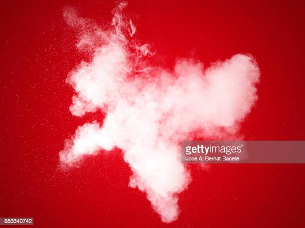 explosion of a cloud of powder of particles of white color on a red bottom - bildeffekt stock-fotos und bilder