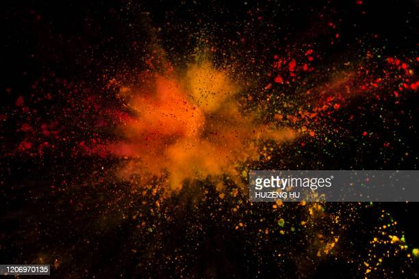 explosion of colored powder on black background - orange burst stock pictures, royalty-free photos & images