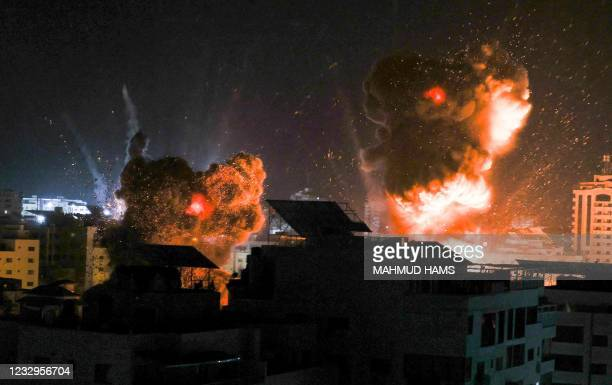 Explosions light-up the night sky above buildings in Gaza City as Israeli forces shell the Palestinian enclave, early on May 18, 2021. - Israeli jets...