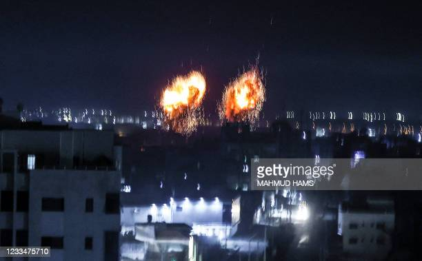 Explosions light-up the night sky above buildings in Gaza City as Israeli forces shell the Palestinian enclave, early on June 16, 2021.