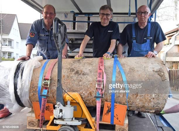 Explosive ordnance disposal personnel Rainer Woitschek KarlHeinz Clemens and Gerd Mathee standing behind a defused warera aerial bomb that was found...