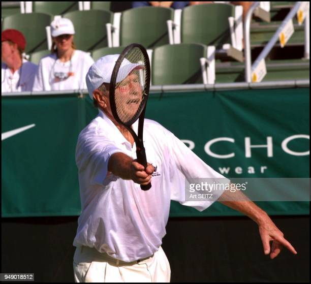 ExPresident George Bush is frame by his racquet as he hits a volley Evert announced that $100000 of the monies raised this year would be donated to...