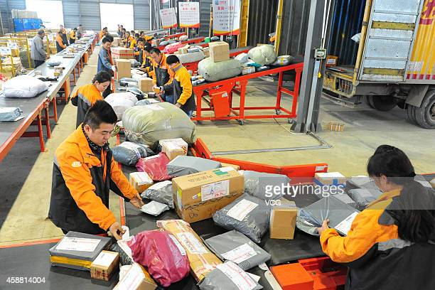 STO express crew deal with express packages delivered from Shanghai at assembly line on November 5 2014 in Fuyang China Online shopping websites...