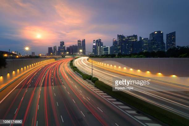 express way in singapore. aerial view of singapore business district and highway at sunset - billboard highway stock pictures, royalty-free photos & images