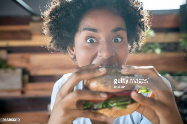 expressive african american woman eating a delicious vegan burger - cibo pronto foto e immagini stock
