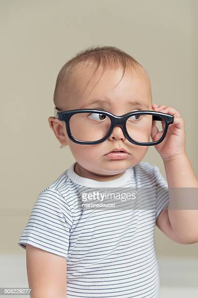 Expressive baby boy with false glasses and striped t-shirt.