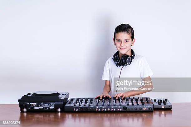 Expressive little boy DJ in headphones mixing up some party music