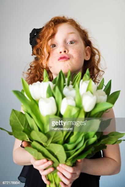 Expressieve redhair meisje met een witte tulpen boeket.