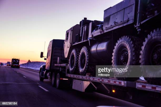 expressway flatbed semi truck convoy hauling armored military land vehicles - trucking stock pictures, royalty-free photos & images
