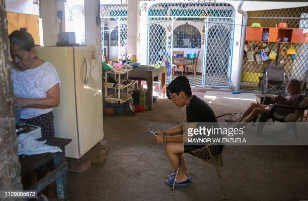 Exprisoner university student Ana Gabriela Nicaragua checks her phone as her mother Juana Lopez cookes at their house in Managua on March 06 2019...