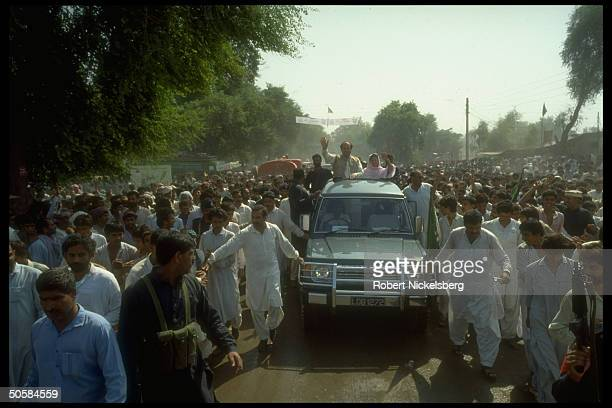 ExPunjab Chief Min Mian Nawaz Sharif Islamic People's Party ldr riding in open car w Govt Min Abida Hussain during IJI election campaign in Punjab