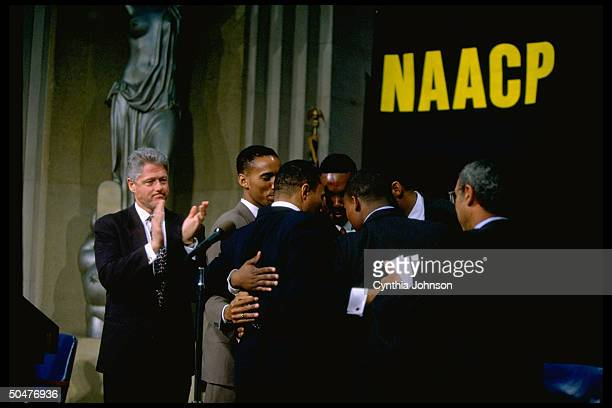 ExRep Kweisi Mfume hugging 4 of his 5 sons as Pres Bill Clinton claps during former's swearin ceremony assuming chmnship of NAACP
