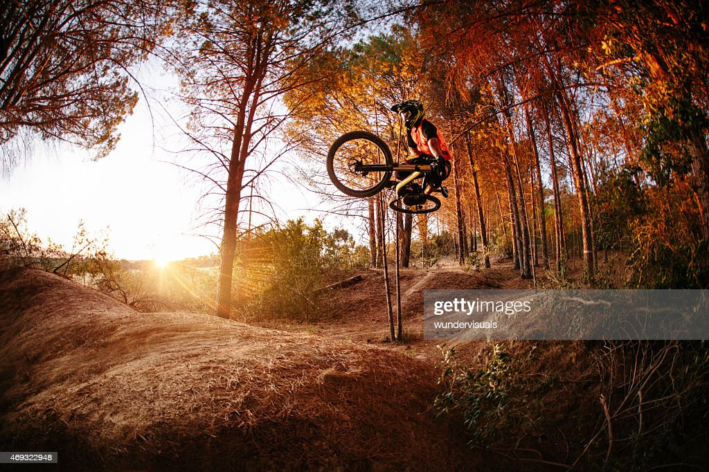 Exteme mountain biker performing aerial maneuvers while dirt jum : Stock Photo
