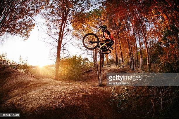 Exteme mountain biker performing aerial maneuvers while dirt jum