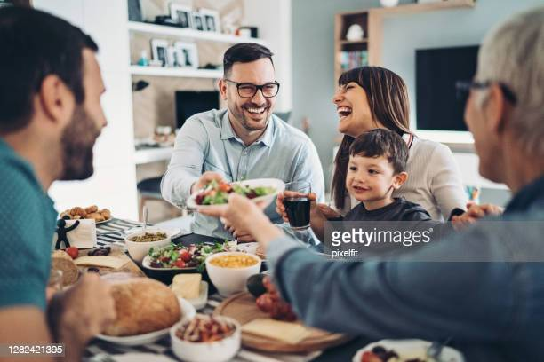 extended family eating together - guest stock pictures, royalty-free photos & images