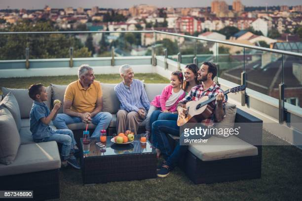 extended family enjoying in a sound of acoustic guitar on a penthouse terrace. - penthouse girls stock pictures, royalty-free photos & images
