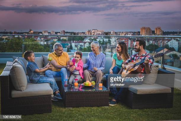 extended family enjoying in sounds of acoustic guitar on a penthouse terrace. - penthouse girls stock pictures, royalty-free photos & images