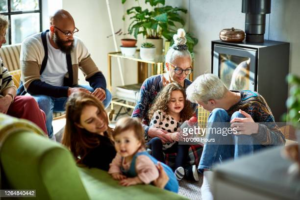 extended family gathering in living room - multiracial group stock pictures, royalty-free photos & images