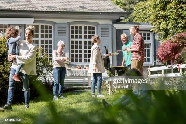 extended family having a barbecue in garden - middelgrote groep mensen stockfoto's en -beelden