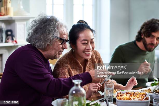 extended family having meal together - real people stock pictures, royalty-free photos & images