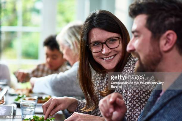 extended family having meal together - 40 44 years stock pictures, royalty-free photos & images