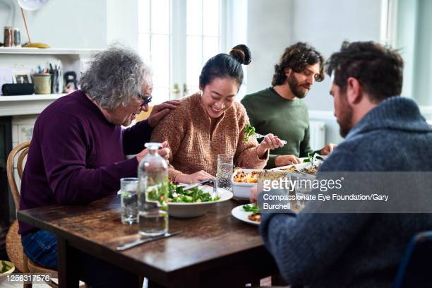 extended family having meal together - four people stock pictures, royalty-free photos & images