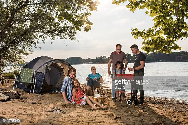 Extended family making barbecue during camping day by the river.
