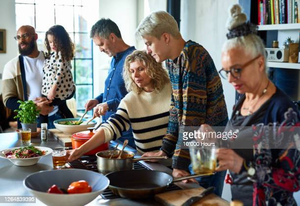extended family preparing dinner together at home - medium group of people stock pictures, royalty-free photos & images