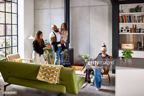 extended family relaxing in living room - modern stock pictures, royalty-free photos & images