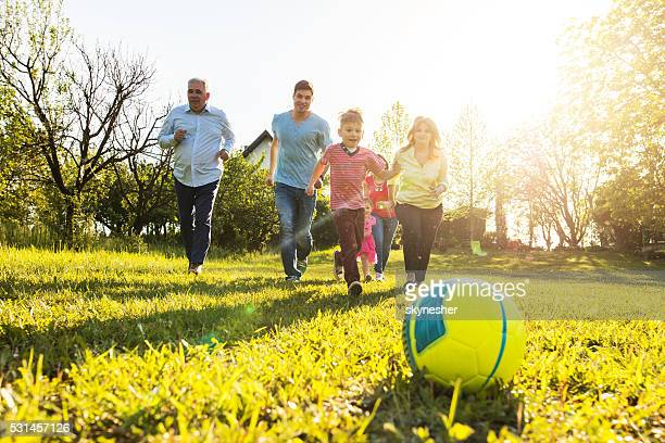Famille courir et jouant avec le ballon dans la nature.