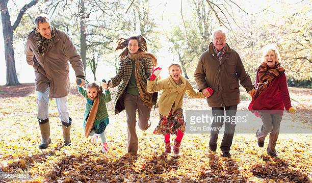extended family running in park in autumn - coat stockfoto's en -beelden