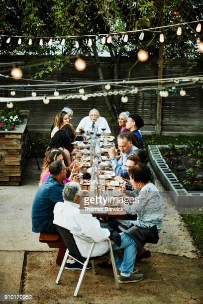 Extended family sharing celebration meal on outdoor patio