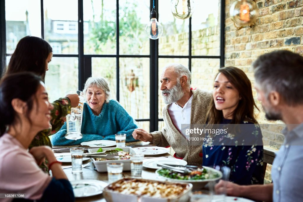 Extended family sitting round dinner table chatting and eating dinner : Foto de stock