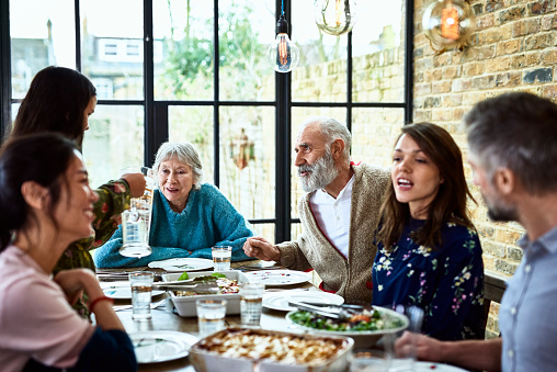 Extended family sitting round dinner table chatting and eating dinner - gettyimageskorea