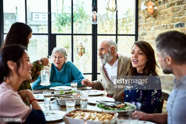 extended family sitting round dinner table chatting and eating dinner - warmes abendessen stock-fotos und bilder