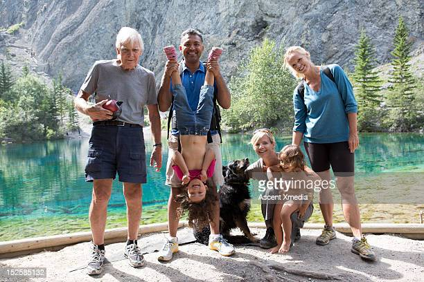 extended family with dog pause beside mtn lake - mixed race person stock pictures, royalty-free photos & images