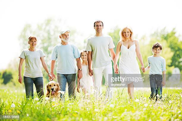 Extended family with grandparents are taking a walk in park.
