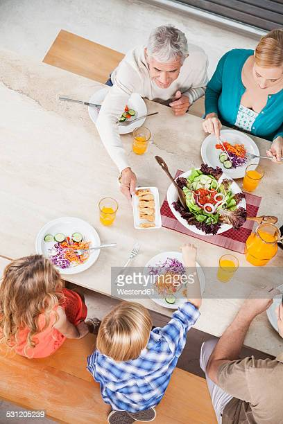 Extended family with salad and juice at dining table