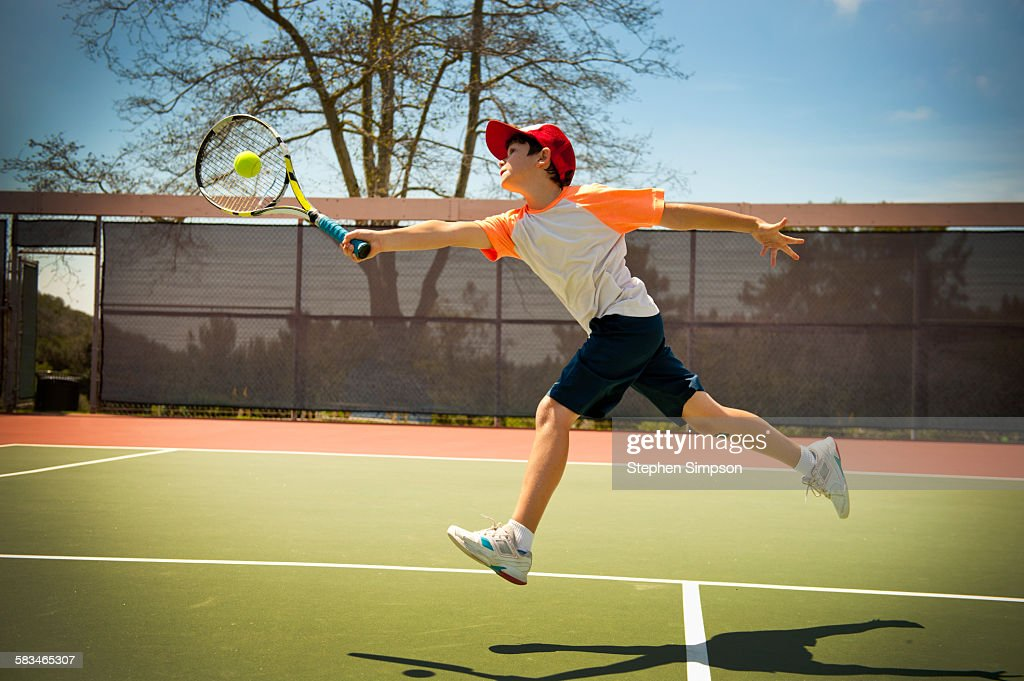 extended reach tennis forehand by young boy : Stock Photo