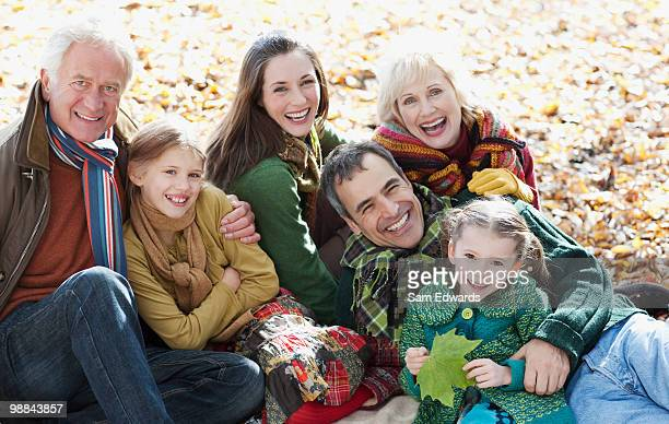 extended sitting in park in autumn - british granny stock photos and pictures