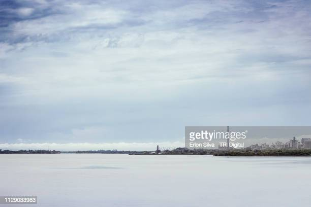 Extensive river on a cloudy day with a city skyline and archipelago brown water