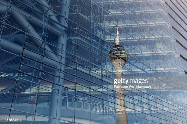 exterior and low angle with detail of reflecting rheinturm, rhine tower, on glass building's facade of stadttor tower against blue sky. - düsseldorf stock-fotos und bilder