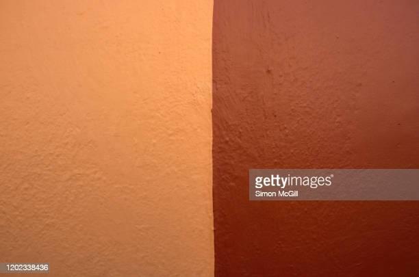 exterior building wall painted apricot orange and dark brown - zweifarbig farbe stock-fotos und bilder