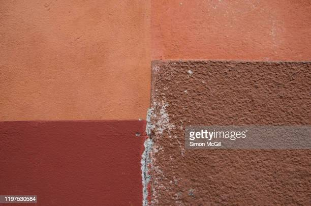 exterior building walls painted salmon pink, maroon and brown - mismatch stock pictures, royalty-free photos & images