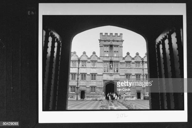 Exterior front view of Oxford's Univ College framed by arched gates w small group of students standing by archway in the distance re Dem presidential...