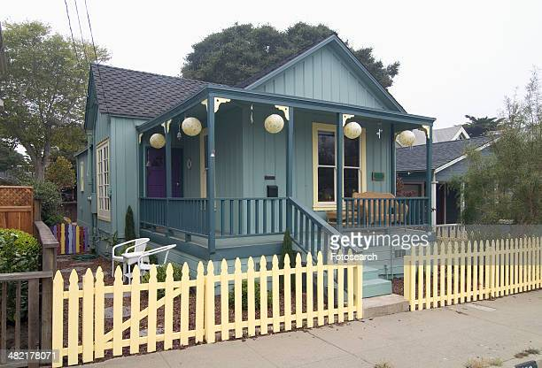 Exterior green American Craftsman styled bungalow with yellow fence