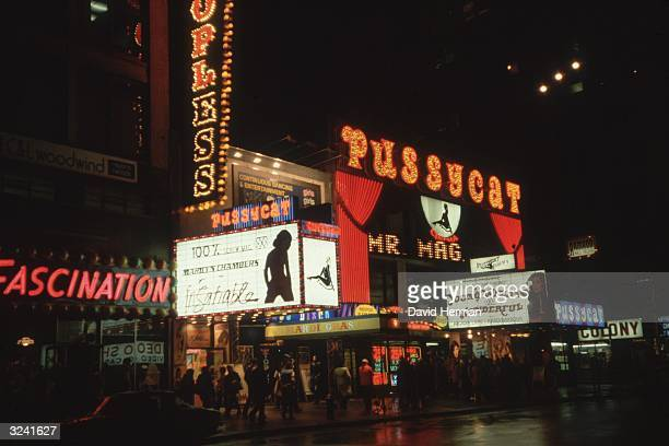 Exterior nighttime view of the Pussycat an Xrated movie theater on 42nd Street in Times Square New York City The marquee advertises porn actor...