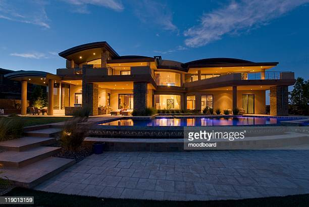 exterior of a building lit up at night with a swimming pool - palm springs california stock pictures, royalty-free photos & images